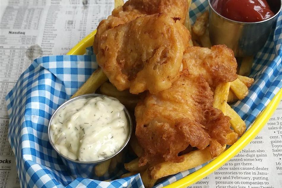 fried fish with french fries and tartar sauce in a yellow basket over newspaper