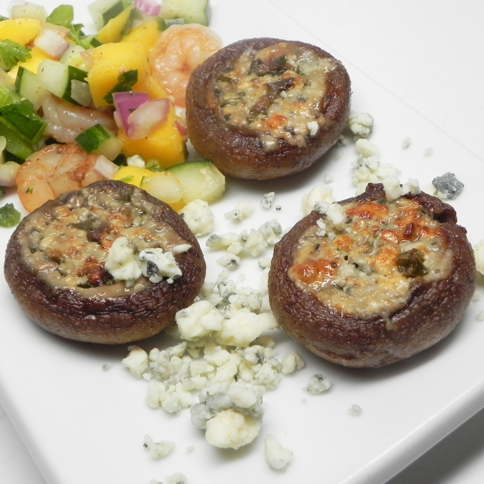 Grilled Mushrooms Stuffed with Basil and Blue Cheese Butter on a white plate