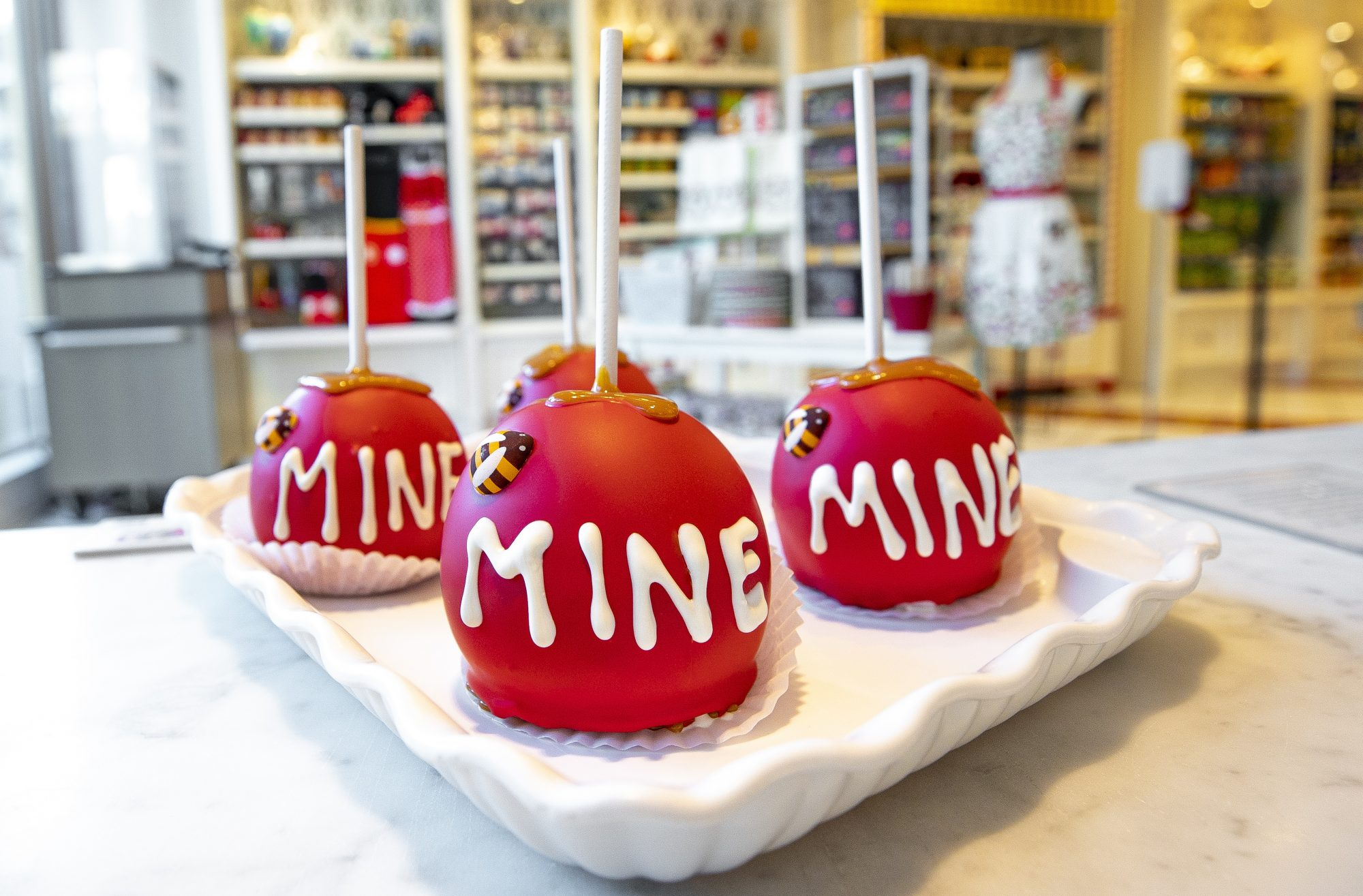 Disney-themed red candy apples with a candy bee and the word mine in frosting
