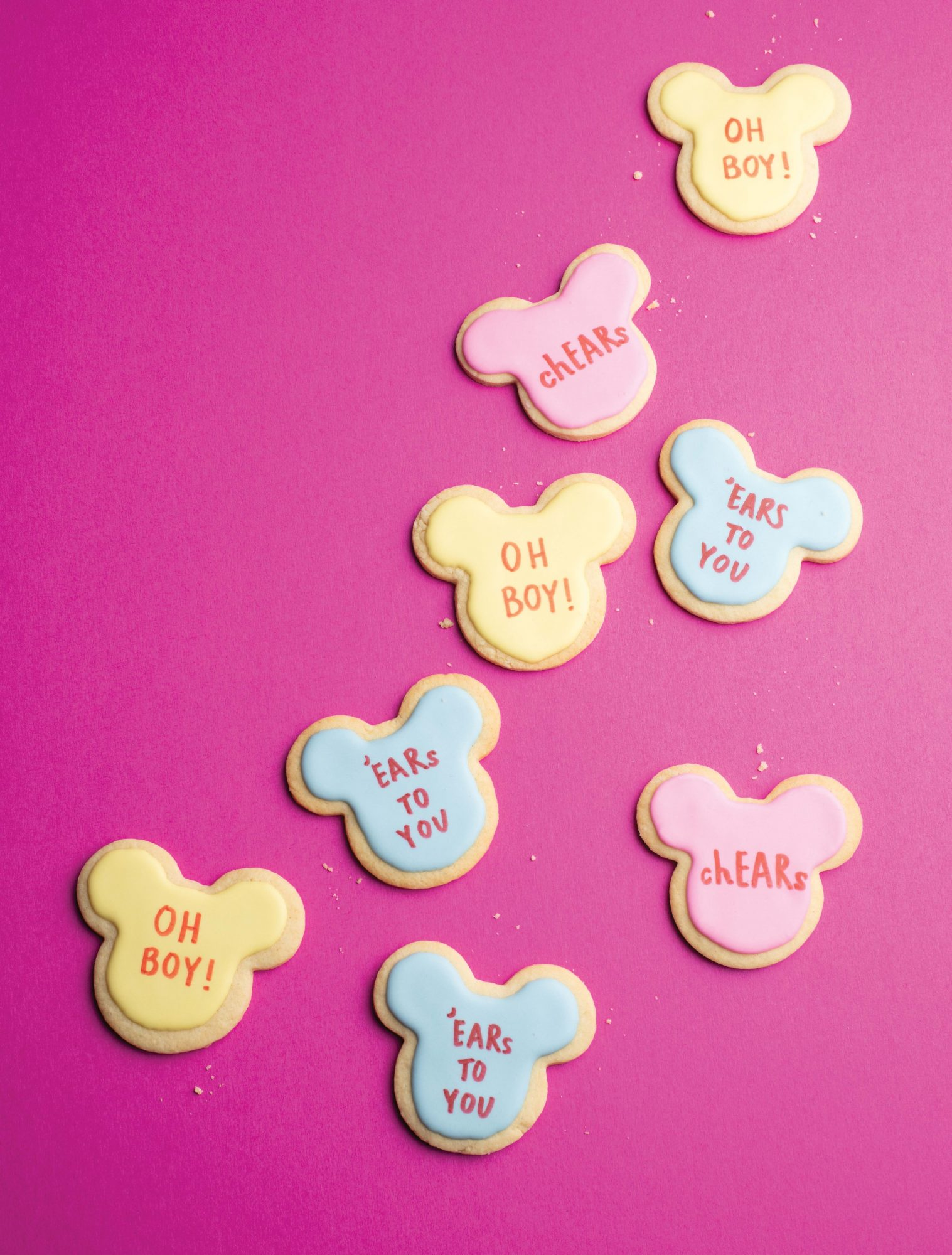 Disney-themed cookies shaped like Mickey Mouse heads with conversation heart messages in frosting