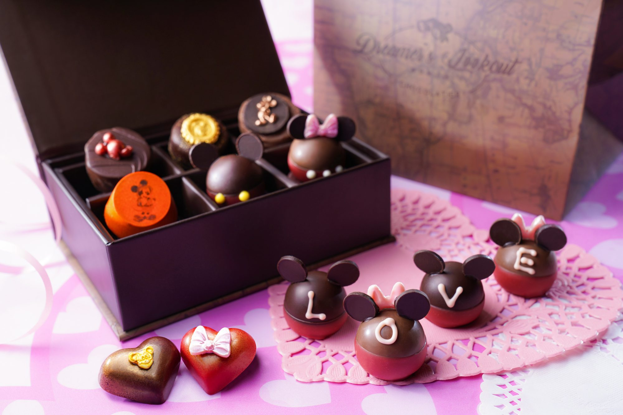 Disney-themed box of chocolates decorated with Mickey Mouse ears, bows, and molded frosting figures