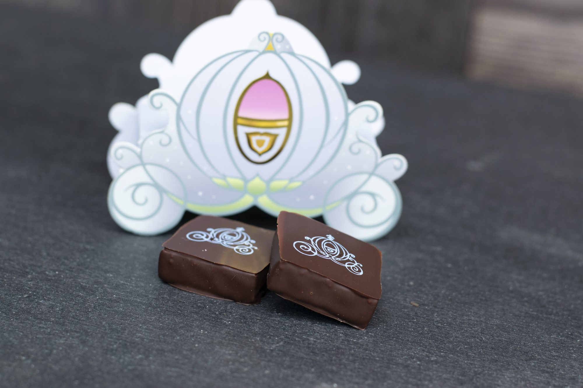 Disney-themed chocolate ganache squares decorated with a white stencil of Cinderella's carriage