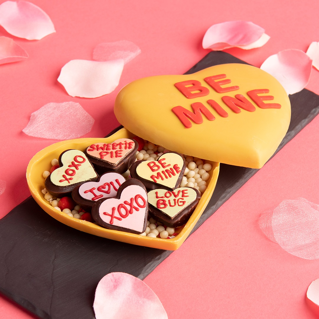 Disney-themed heart-shaped candy box with heart-shaped candies inside, decorated with conversation heart messages