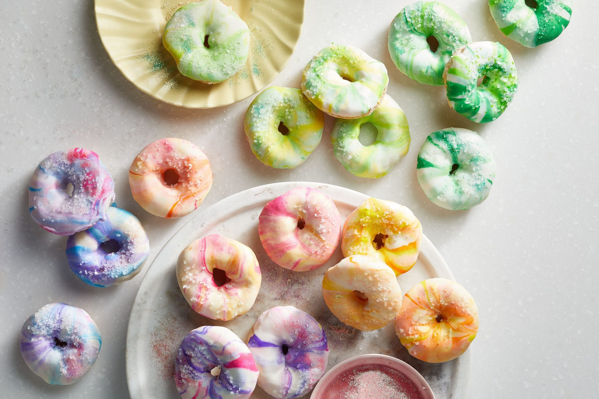 mini doughnuts dip-dyed in shades of blue, red, pink, yellow, orange, and green