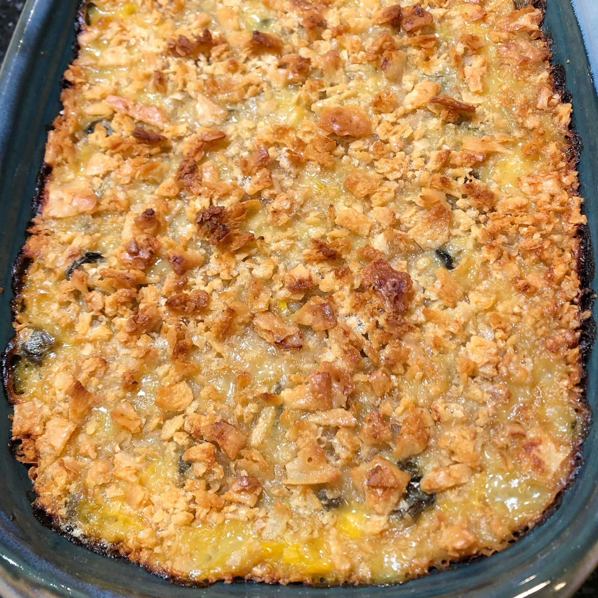 oyster casserole with cheesy topping in a blue stoneware dish