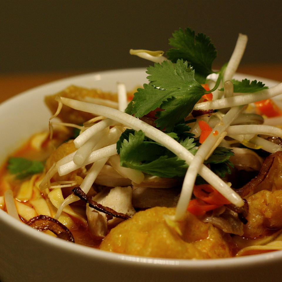 side view of a bowl of chicken and shrimp soup in coconut milk broth, piled with fresh bean sprouts and cilantro
