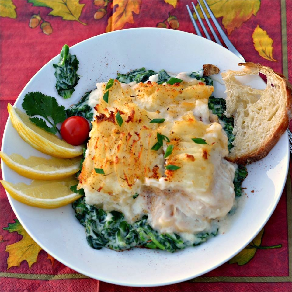 fisherman's pie with spinach garnished with lemons and served with bread