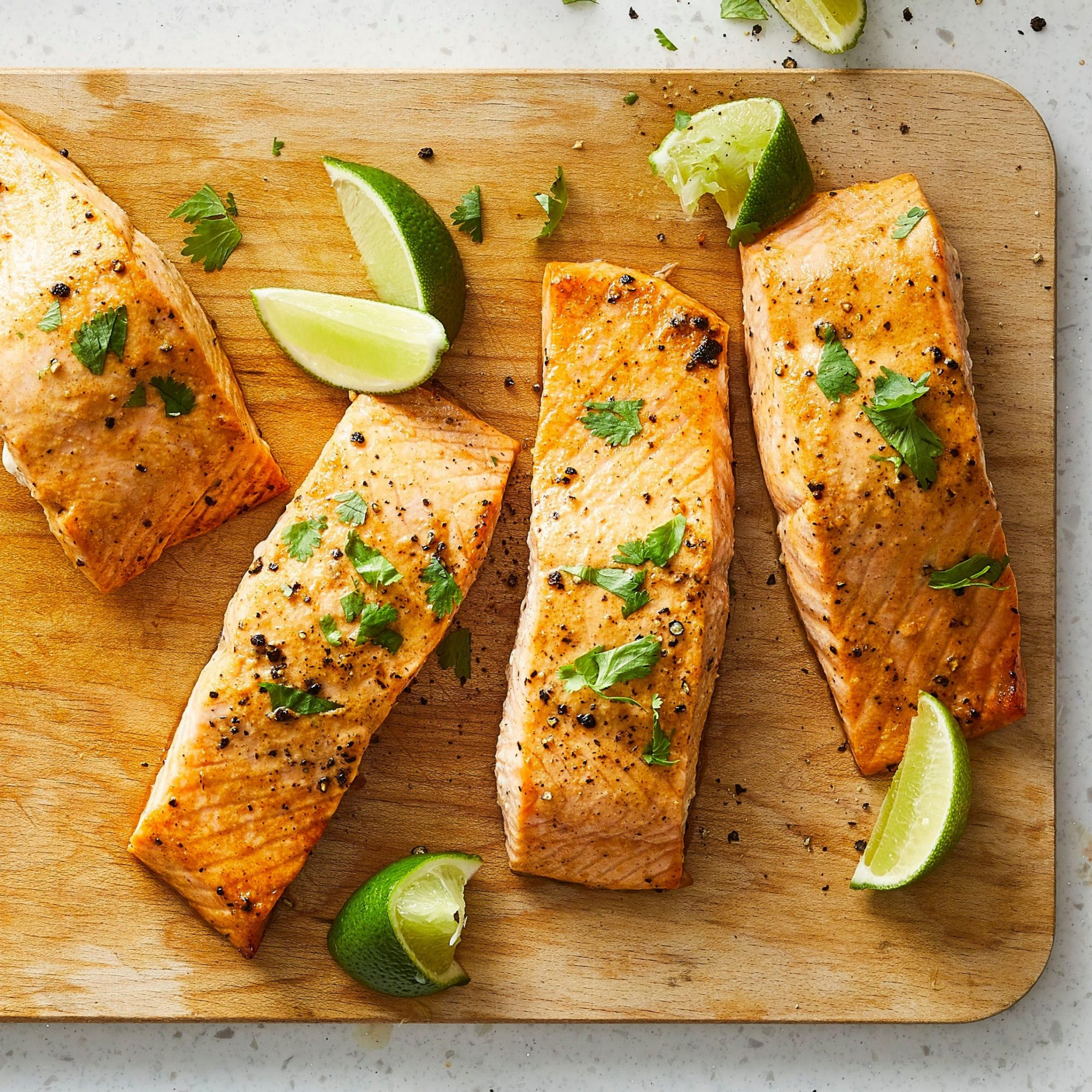 close up of Lime-Marinated Baked Salmon and lime wedges on a cutting board