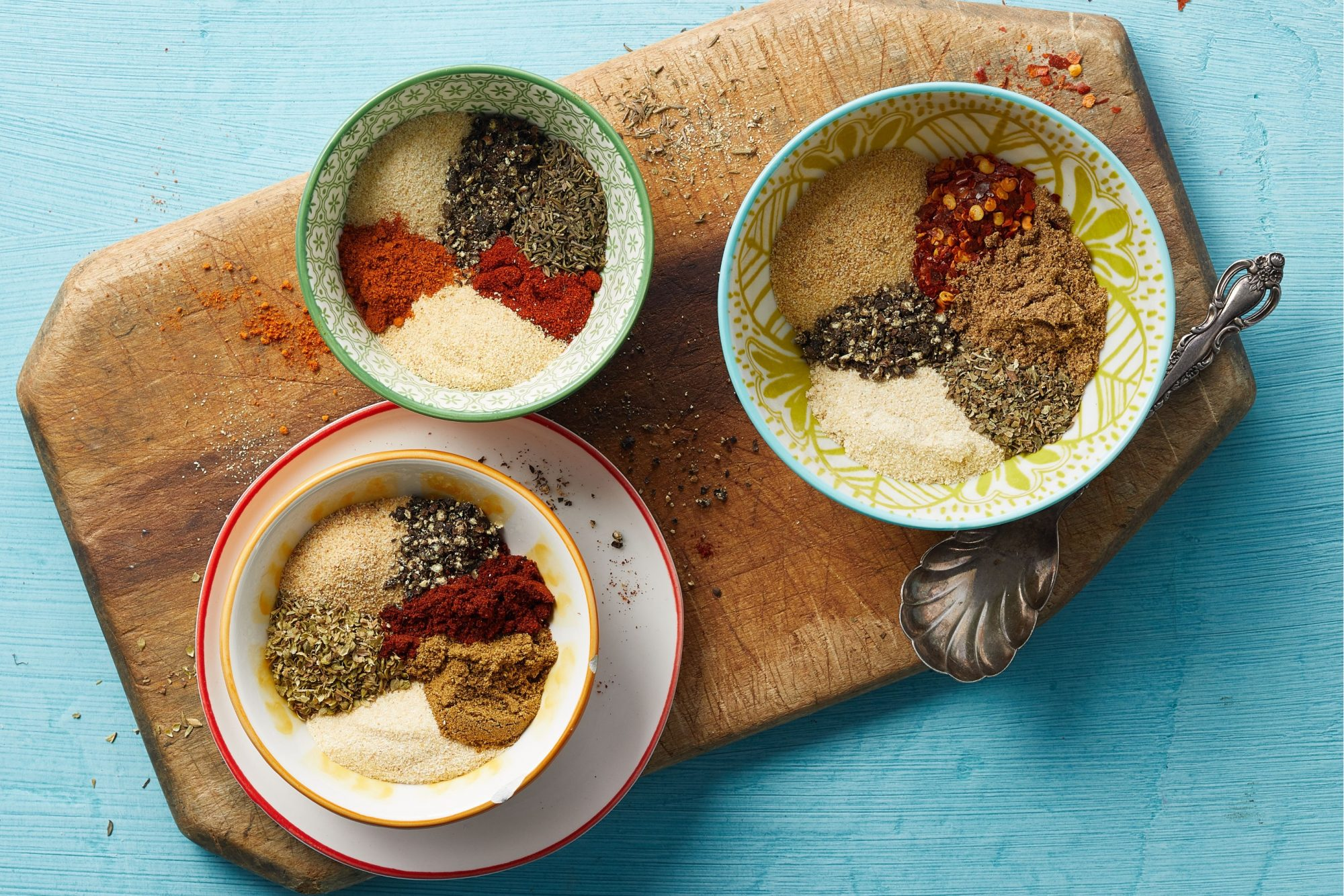 three homemade seasoning mixes in bowls on a cutting board