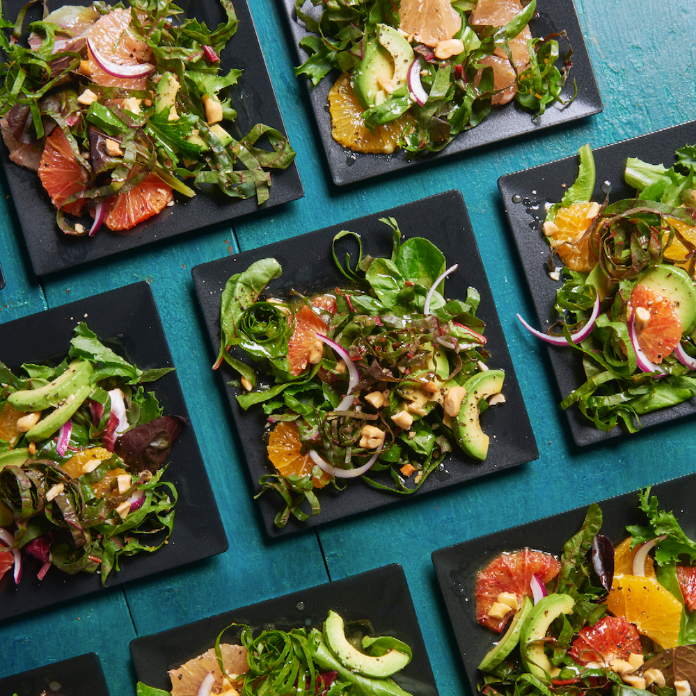 swiss chard, avocado, grapefruit salad on several black square plates