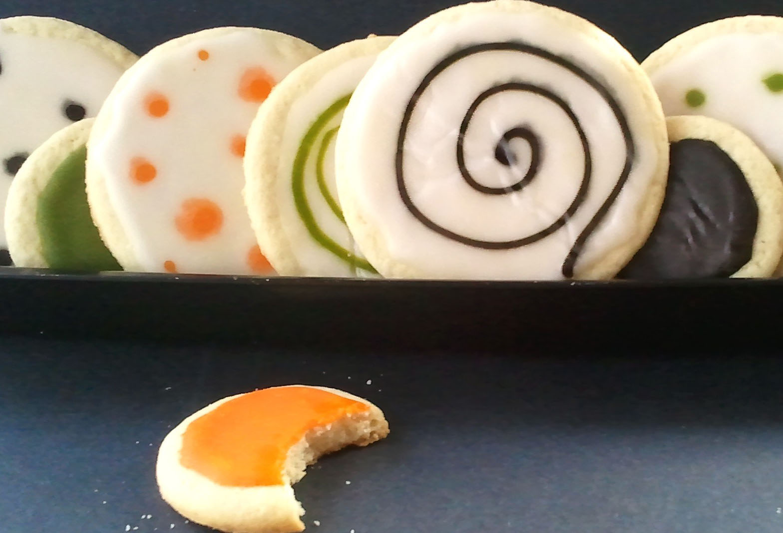 frosted round cookies decorated with swirls and polka dots