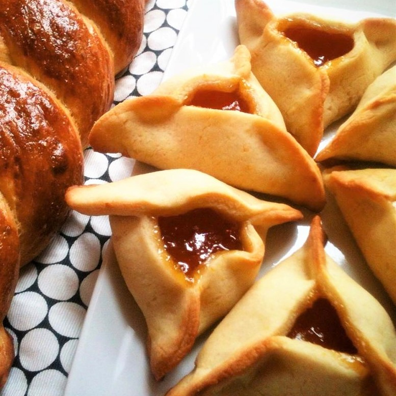a white plate with jam-filled hamantaschen, a Jewish pastry made for Purim