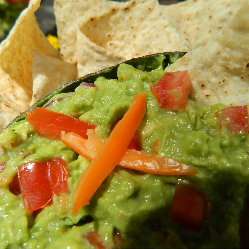 guacamole and tortilla chips up close with chopped peppers