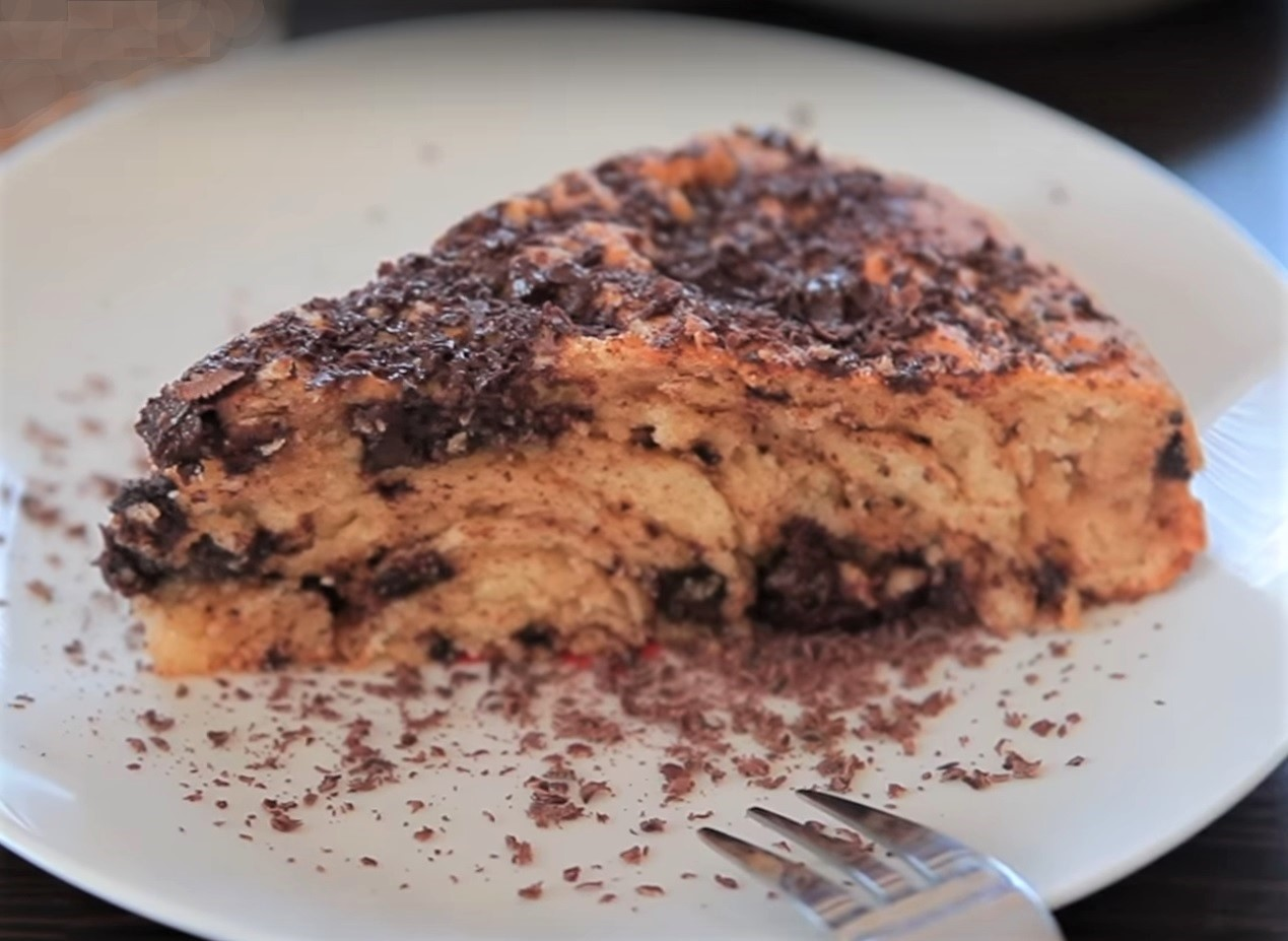 a slice of ricotta cake with chocolate chips and shavings on a white plate with a fork