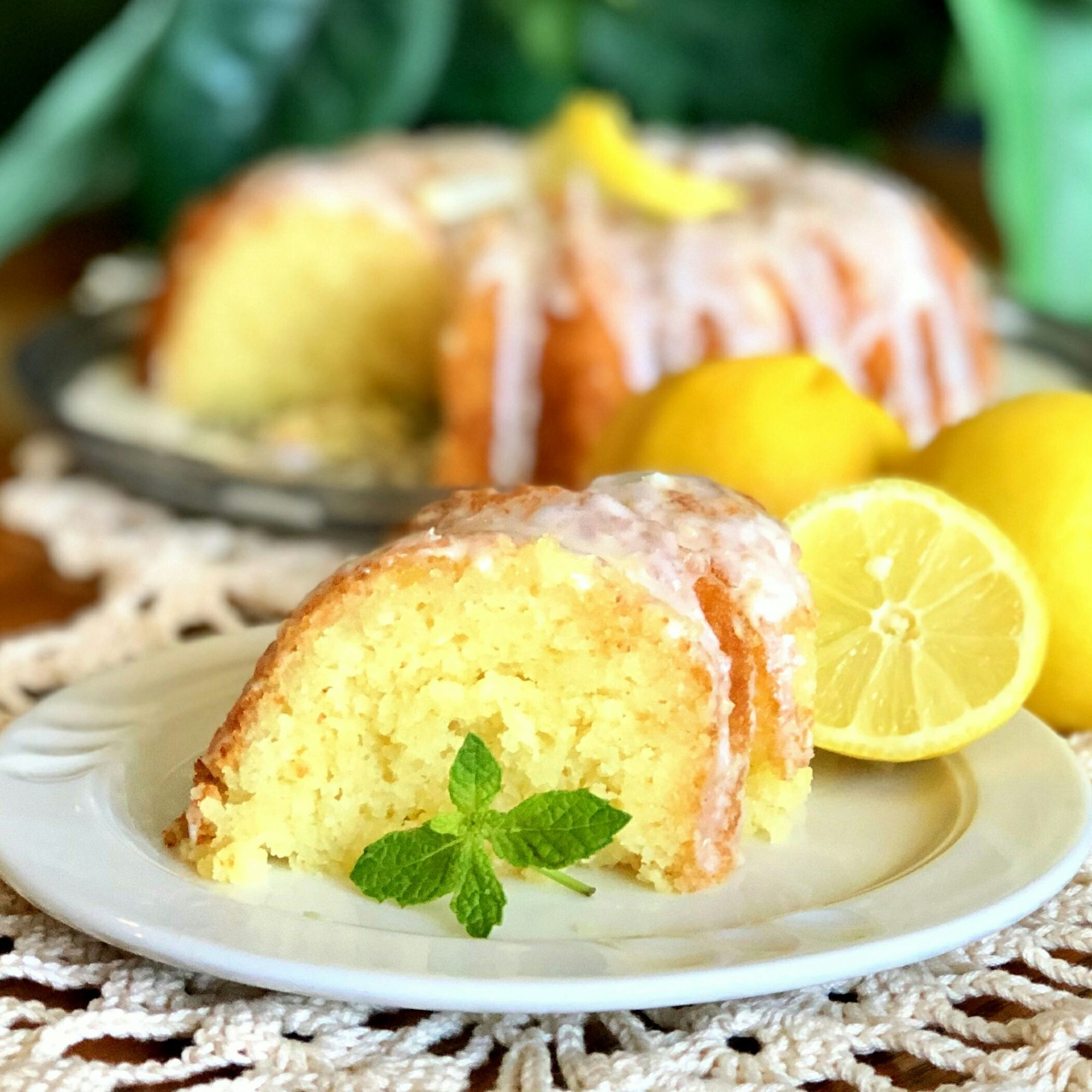 a slice of lemon ricotta cake with the whole cake in the background