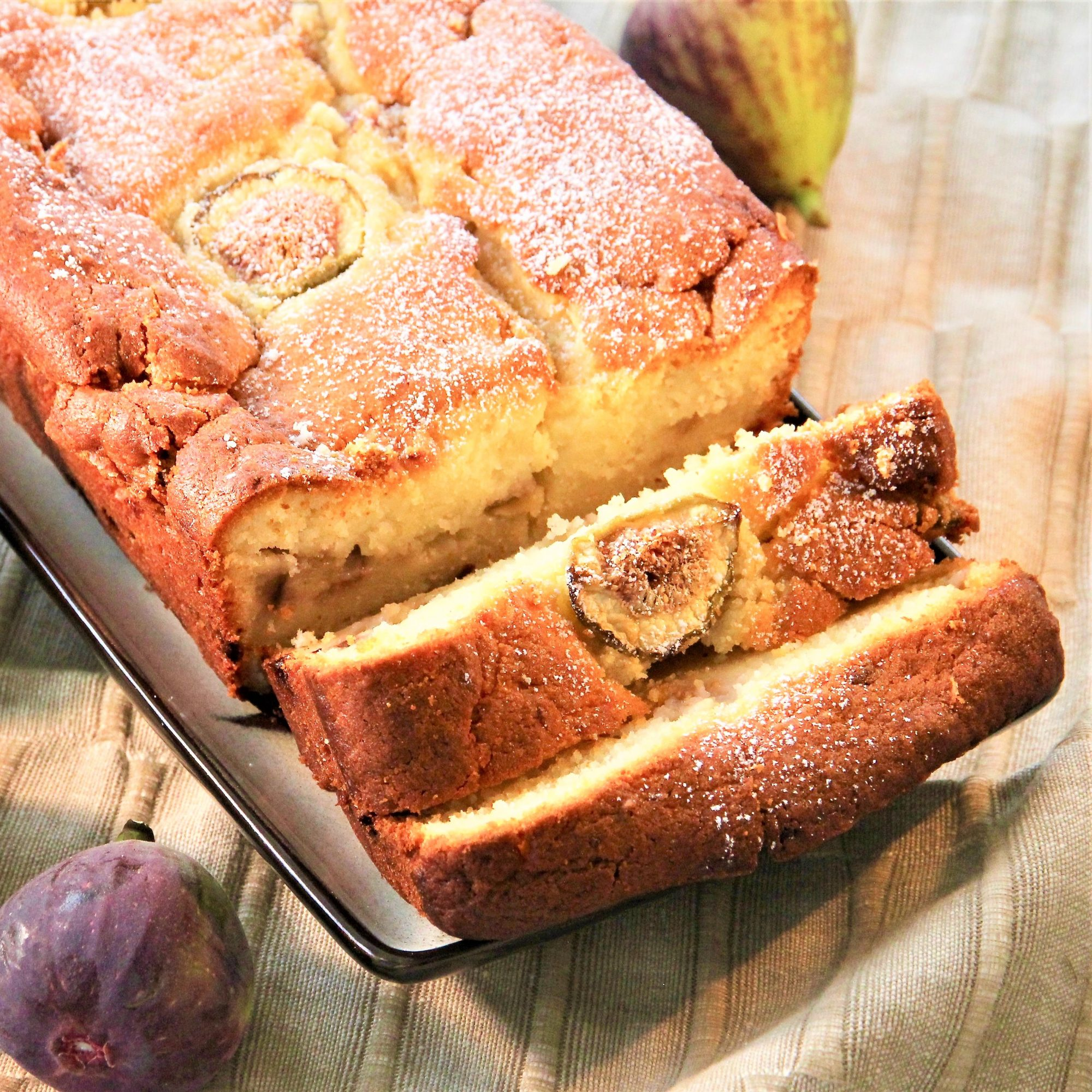 a sliced loaf cake with figs on the side