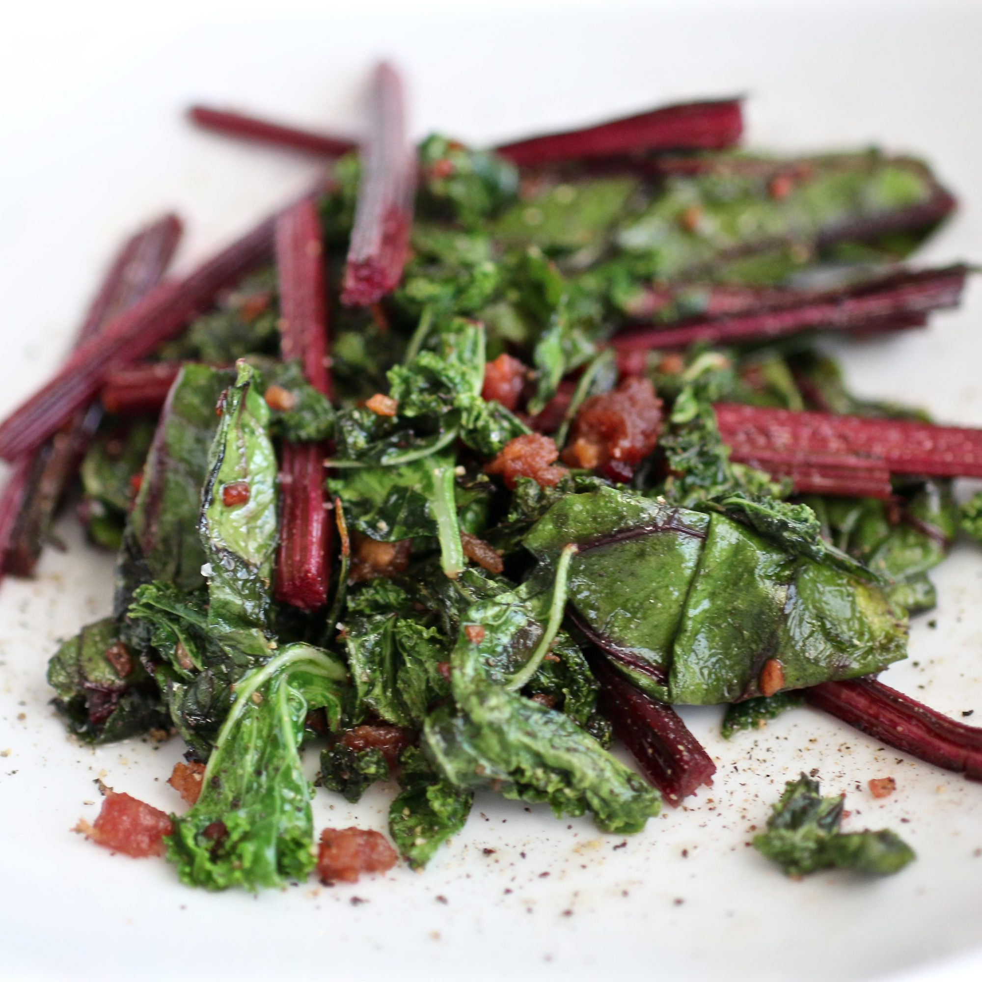 Beet Greens and Kale Sauteed with Bacon and Garlic on a white plate