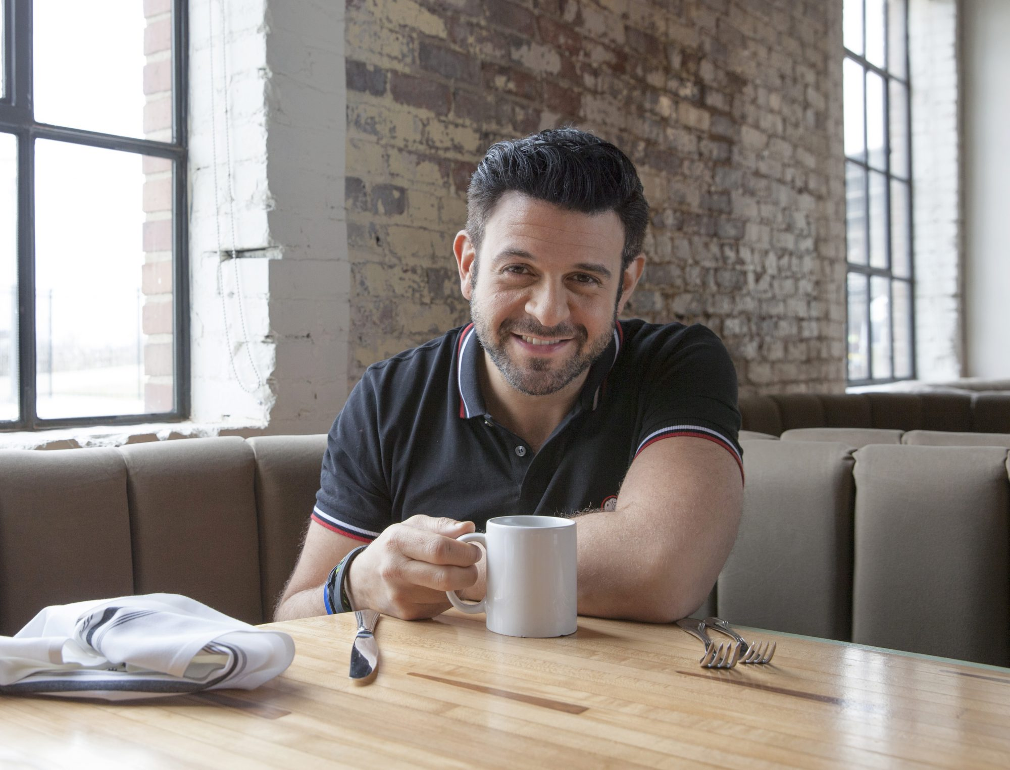 Adam Richman sitting in a booth with a mug on the table