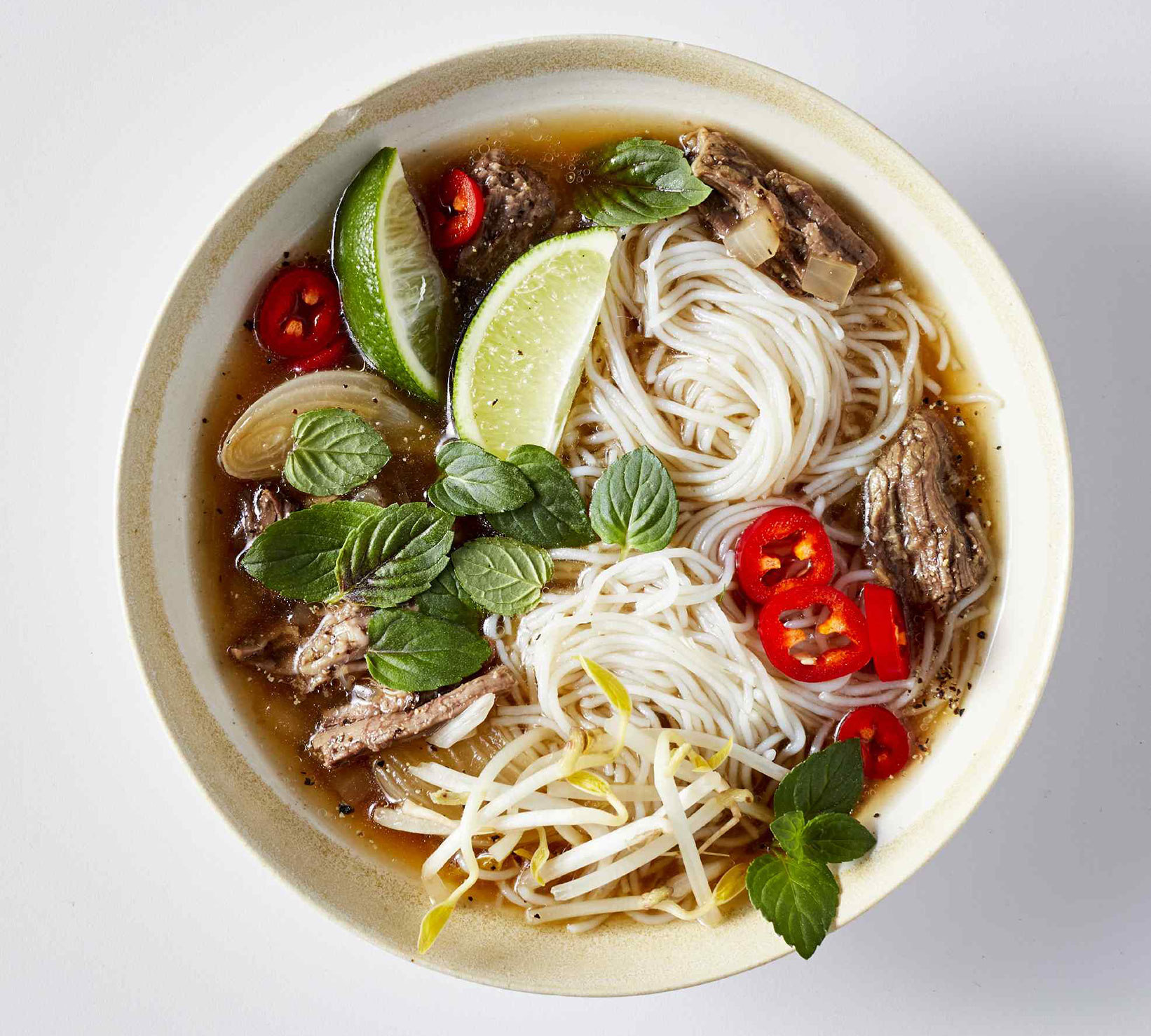 pho with beef, rice noodles, lime, and peppers in clay bowl