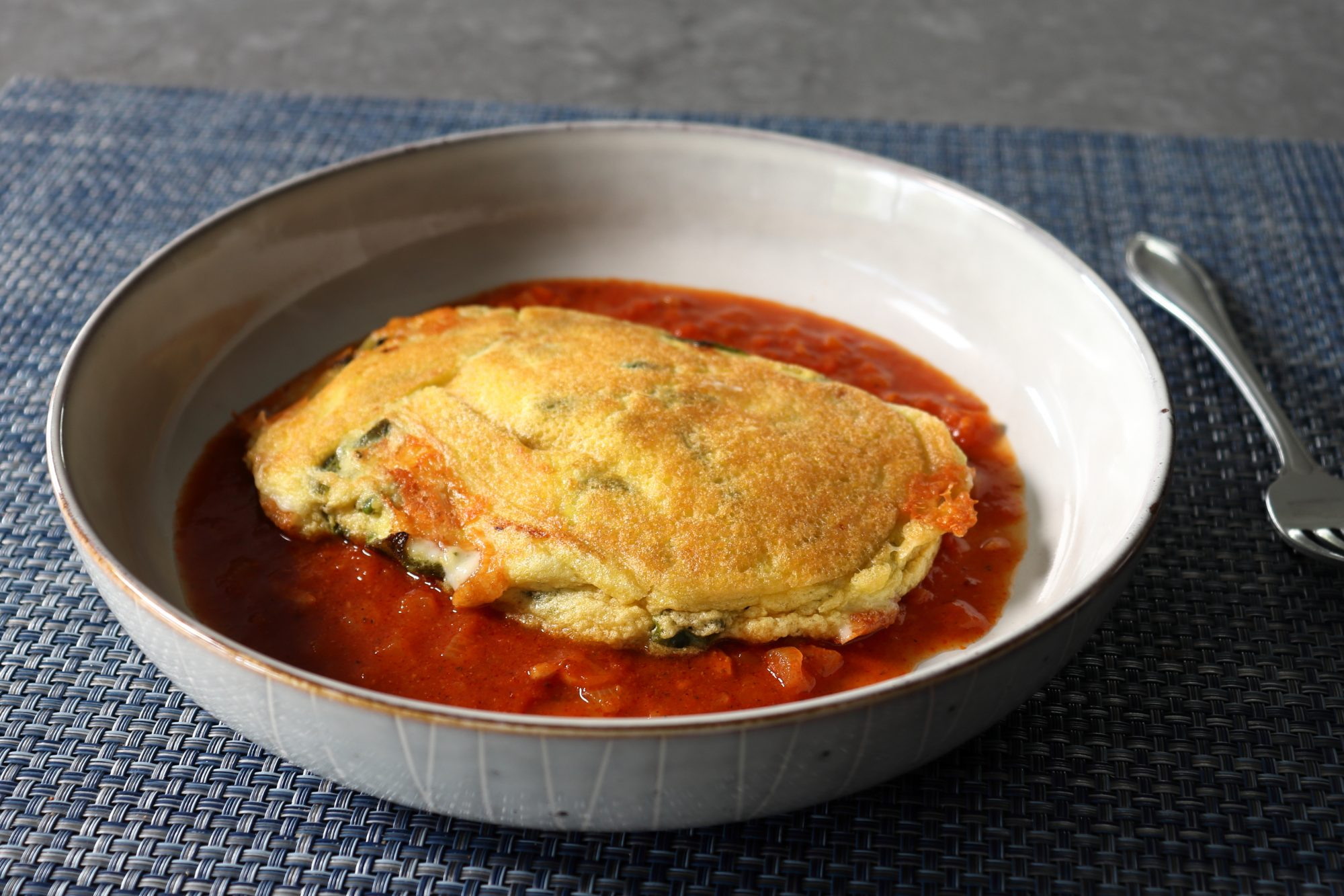 a bowl holding a pancake version of chile relleno on a spiced tomato sauce