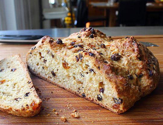 closeup of a cut loaf of soda bread with raisins and currants on a cutting board