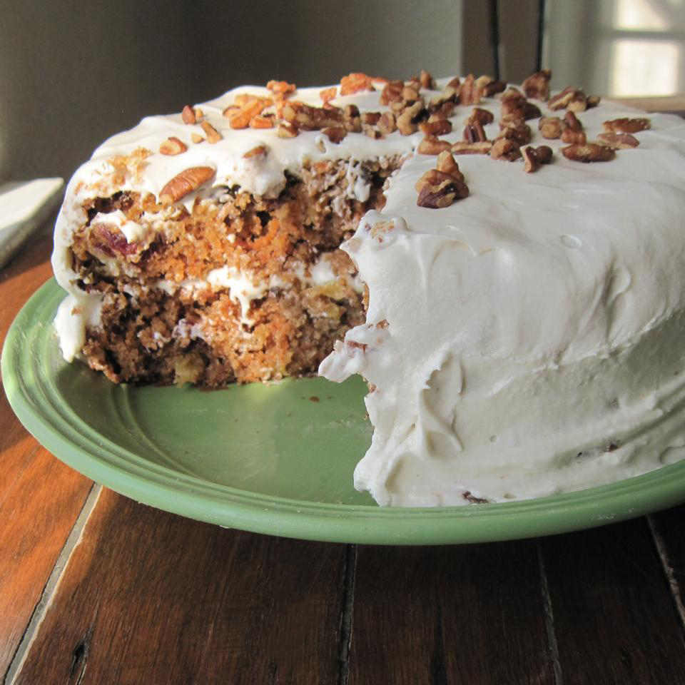 a two-layer carrot cake with cream cheese frosting with a wedge cut out showing the raisins and nuts inside