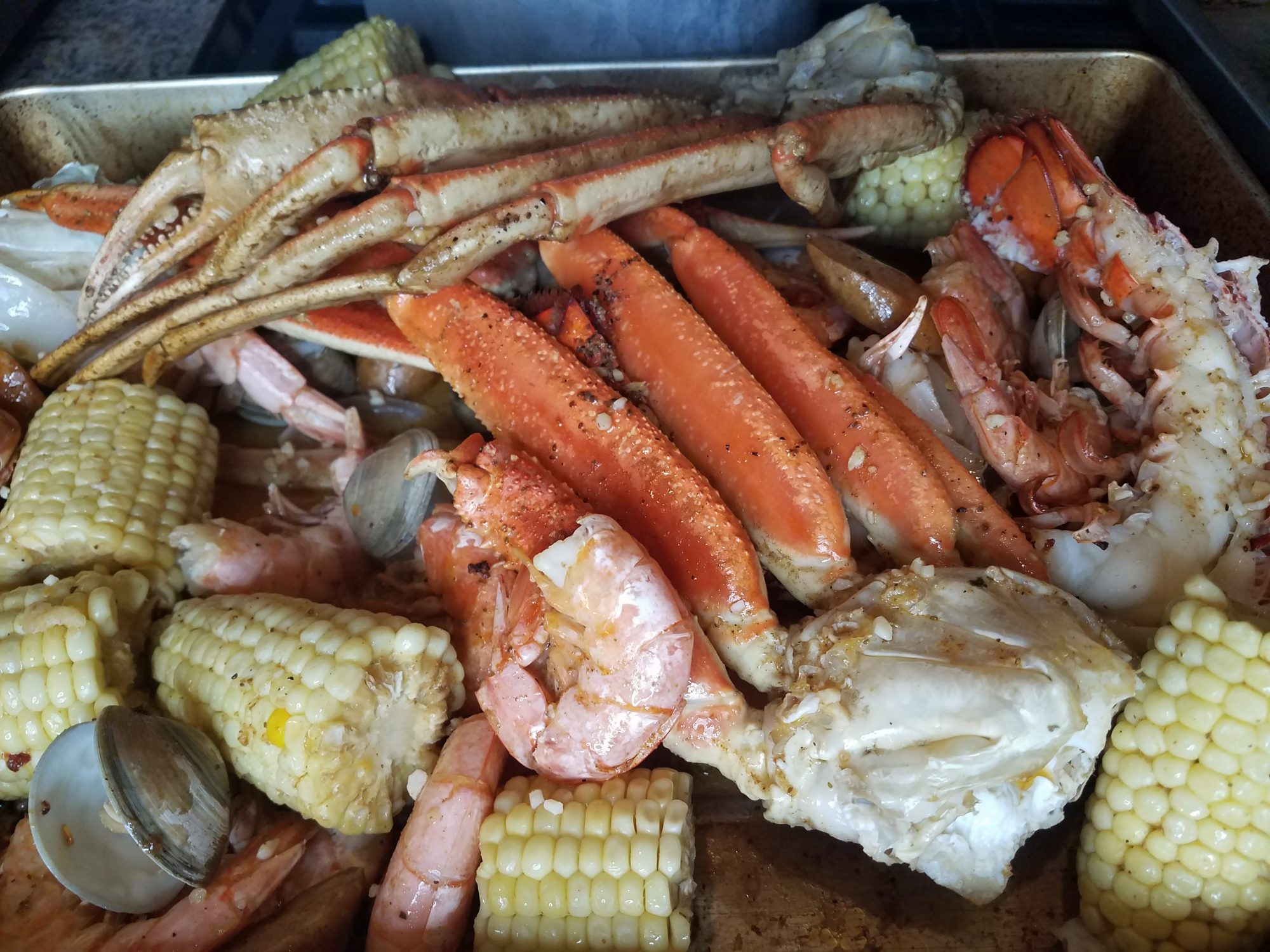 If you are looking for a fun project to impress your family or friends, try your hand at this seafood boil. Clams, shrimp, crab, and lobster mingle on the sheet pan with sausage and corn, covered in a delicious garlic butter sauce with a kick.