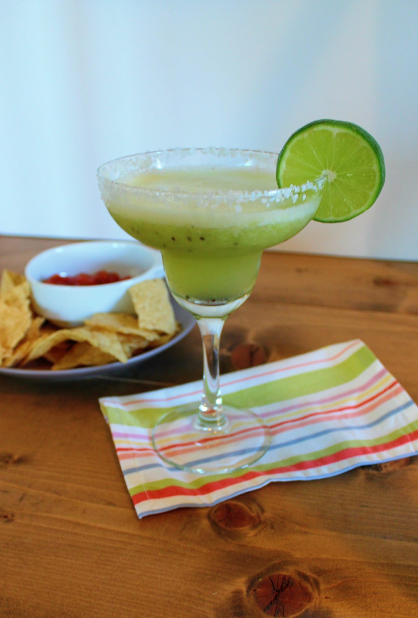 kiwi margarita in margarita with lime garnish in front of chips and salsa