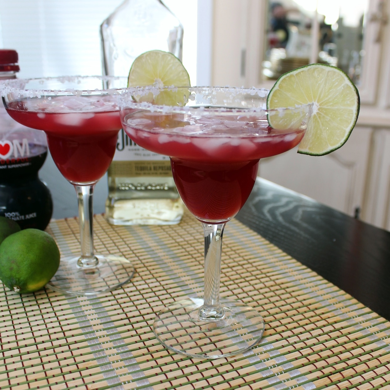pomegranate margaritas in a glass with salt rim and lime wedge