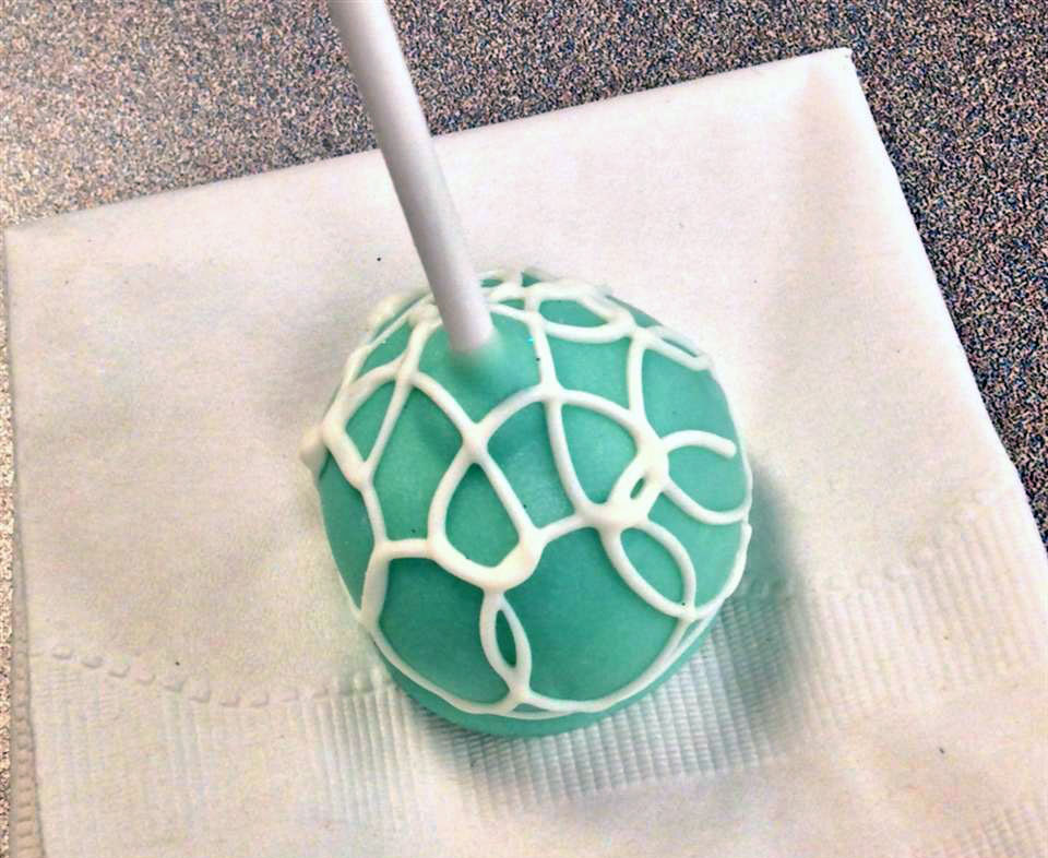 a blue-green cheesecake pop with white piped swirls on a napkin