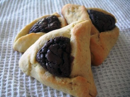 closeup of three triangular cookies with brownie centers on a white cloth