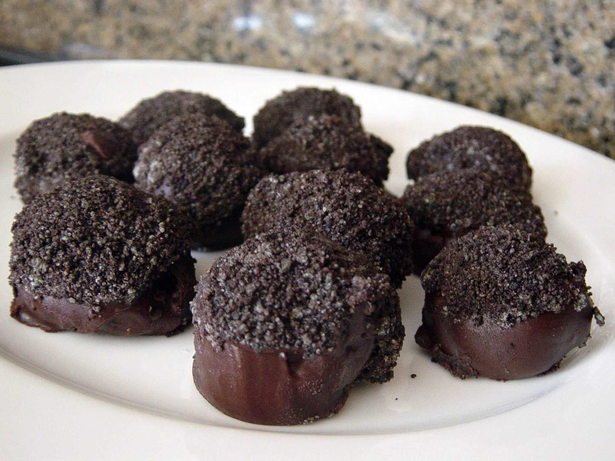 a plate of cookie balls or cake balls coated in chocolate and topped with Oreo cookie crumbs