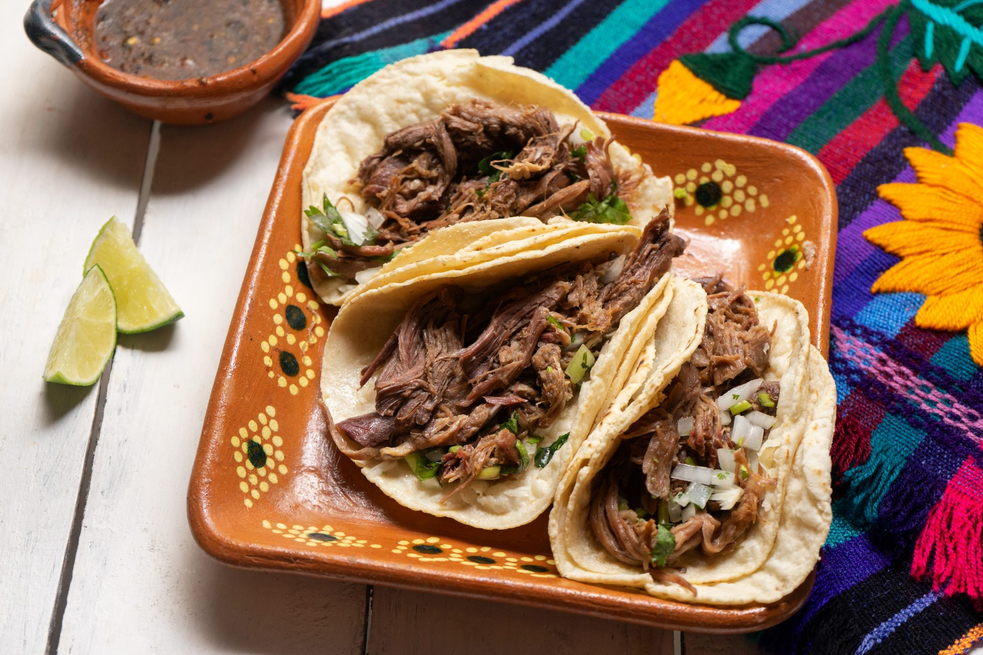 Mexican slow cooked lamb tacos also called barbacoa on white background