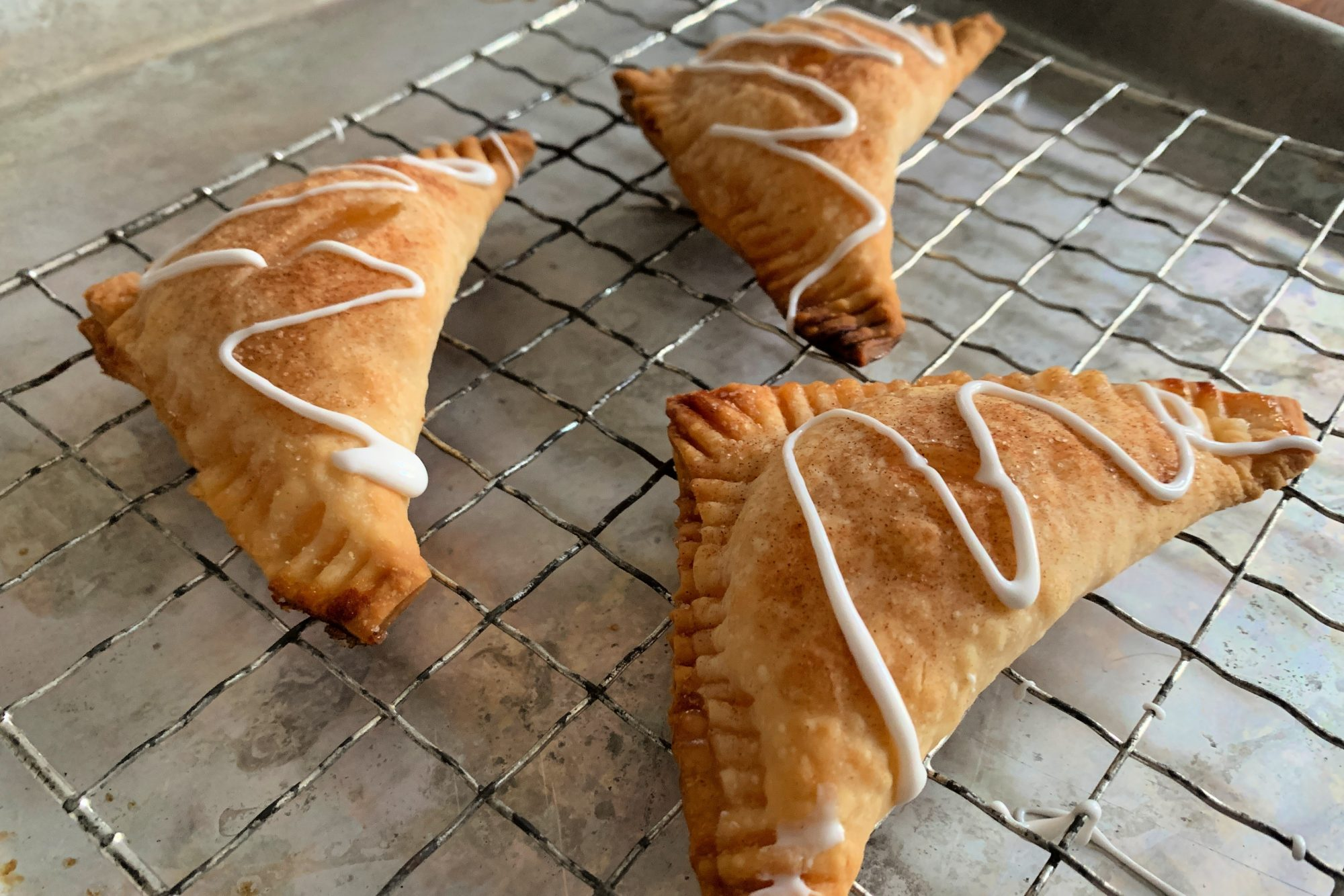 three homemade apple turnovers cooling on a rack