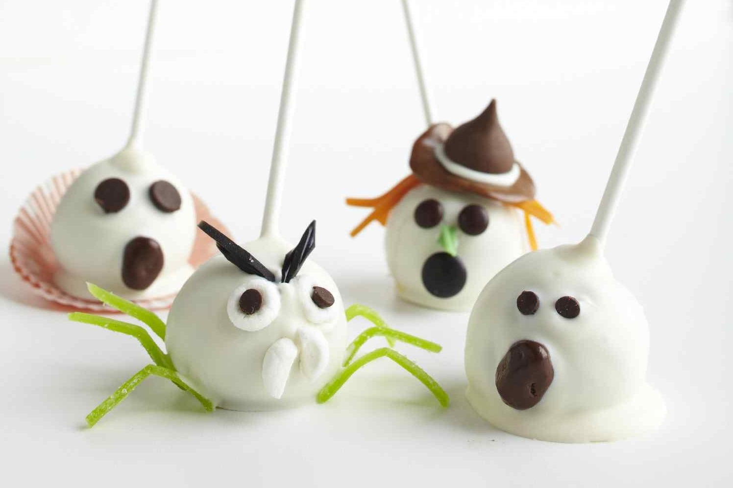 Halloween-themed cake pops dipped in icing and decorated to look like ghosts, witches, and spiders