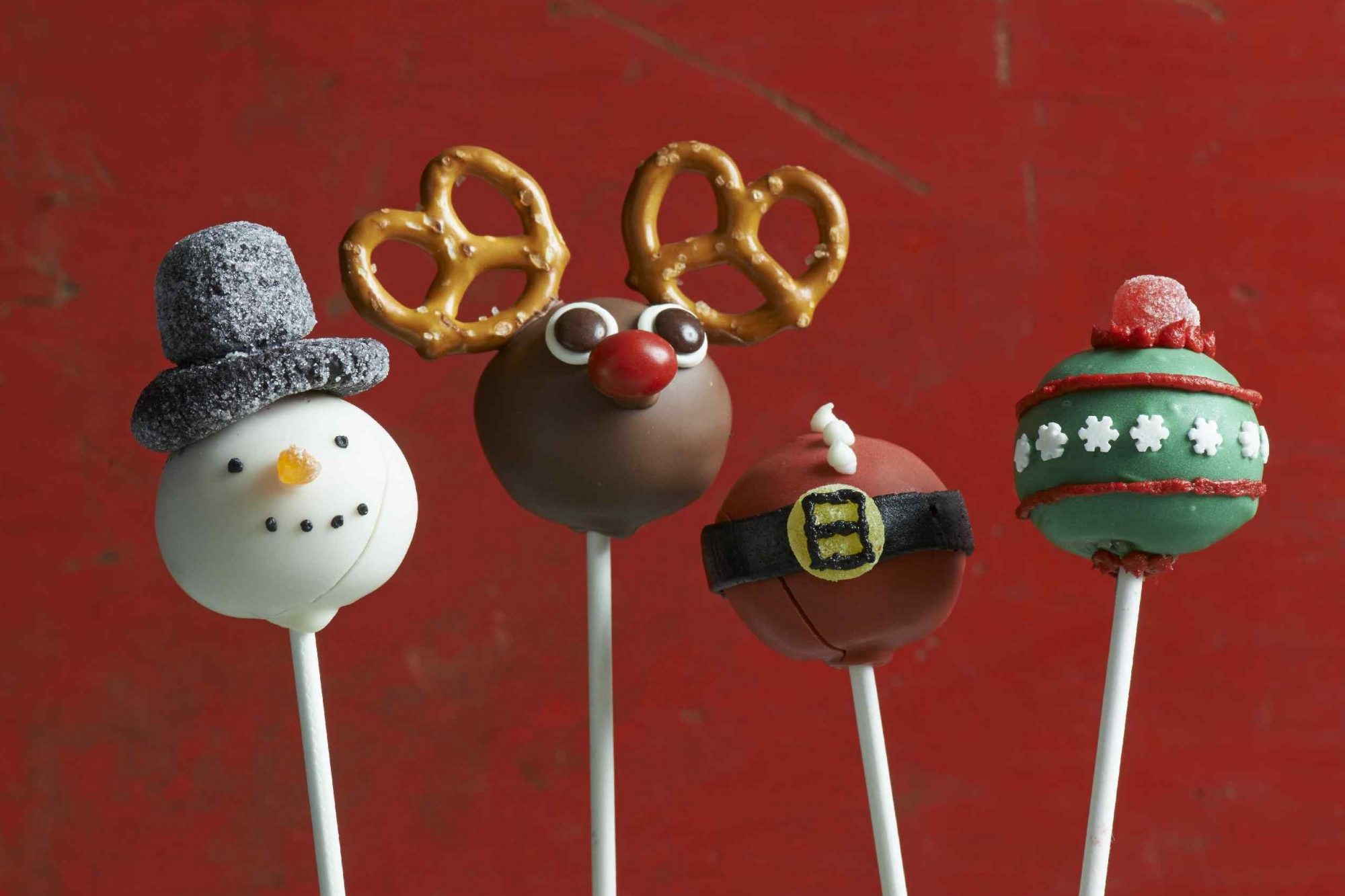 Christmas cake pops decorated to look like snow person, reindeer, Santa's tummy, and a Christmas tree ornament