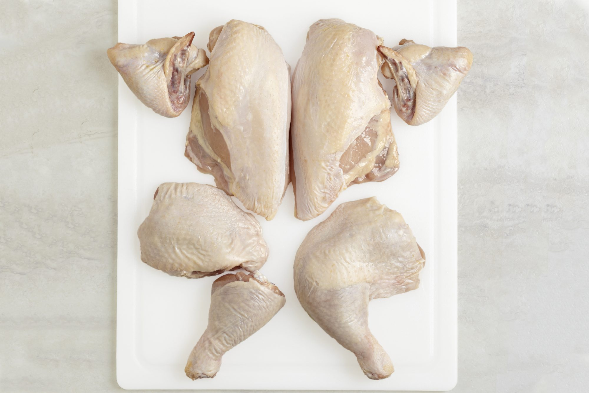 whole chicken broken down into separate parts: wings, breasts, thighs, drumsticks