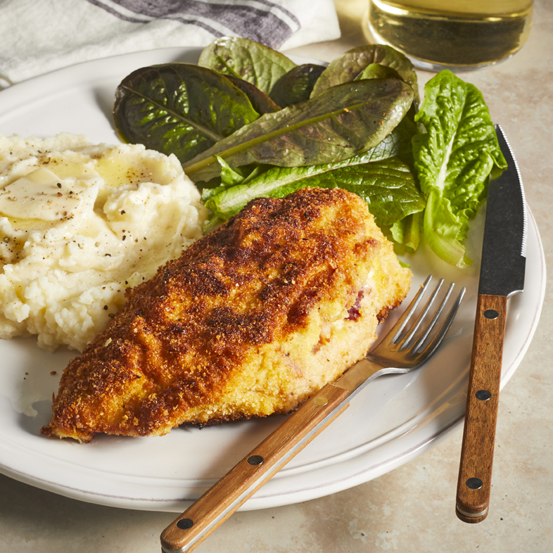 Feta and Bacon-Stuffed Chicken with Onion Mashed Potatoes plated with some salad greens