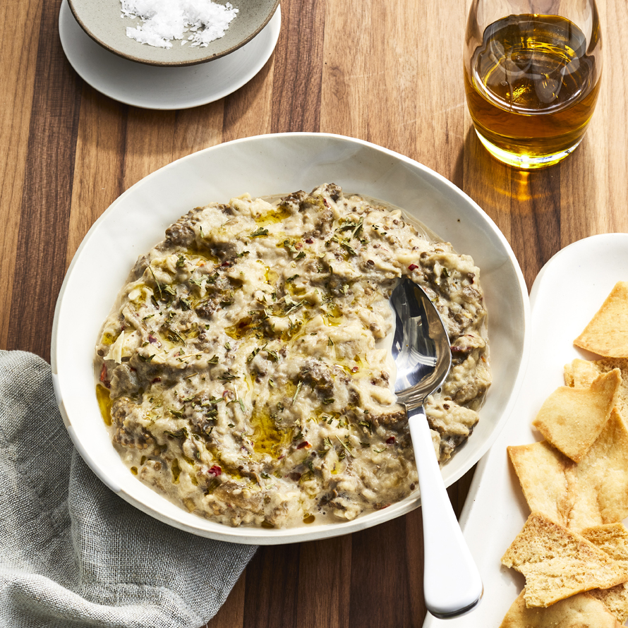 White bowl of Traditional Baba Ghanoush, served with some pita chips.