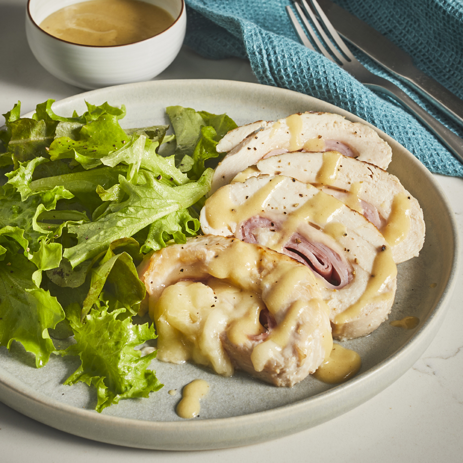 Plate of sliced Chicken Cordon Bleu Rollup drizzled with a honey mustard white wine sauce