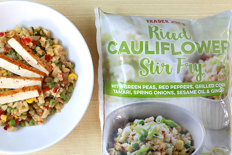 a bag of trader joe's Riced Cauliflower Stir Fry with a bowl of prepared food beside it