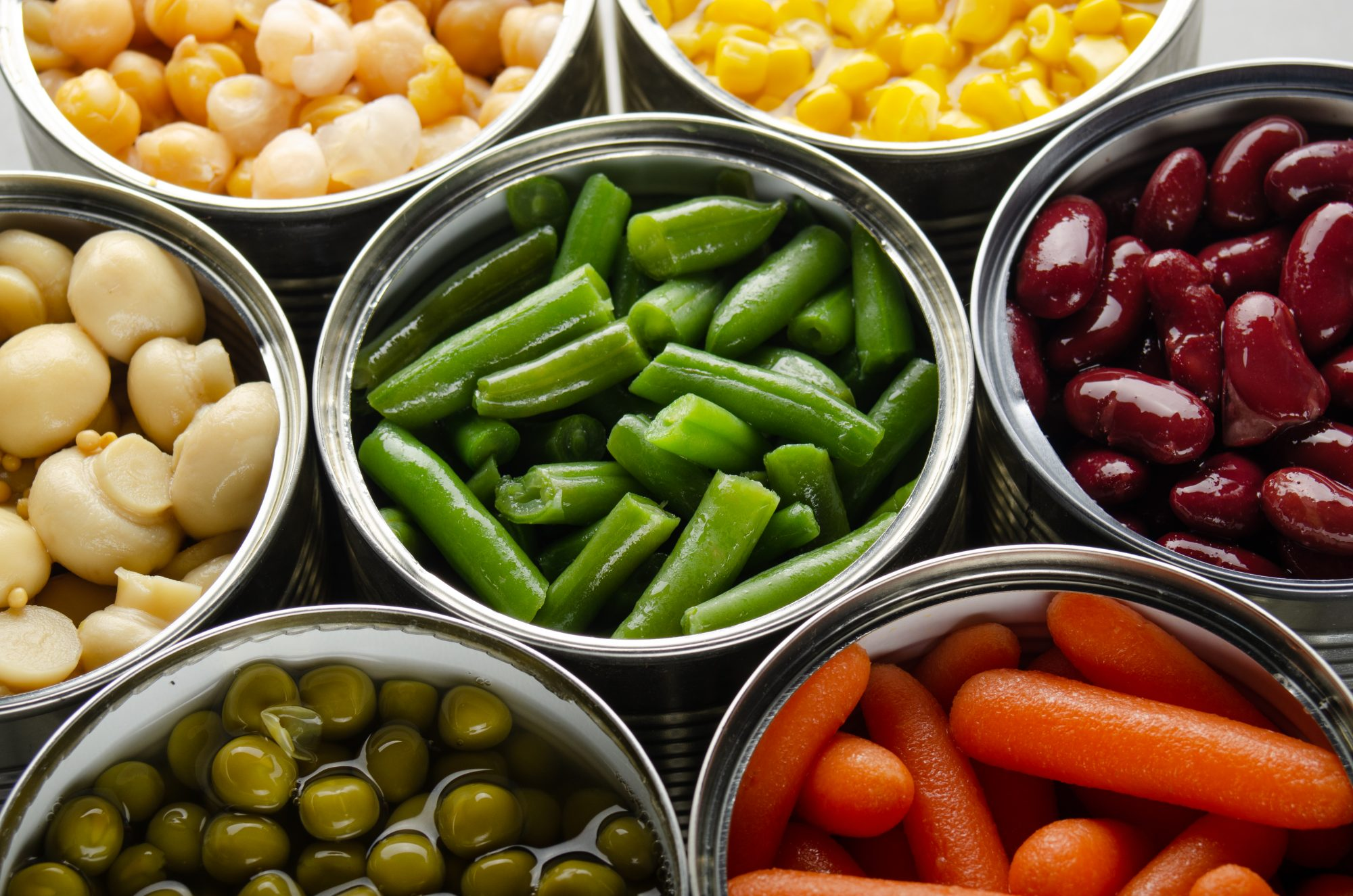 Canned vegetables in opened tin cans on kitchen table. Non-perishable long shelf life foods background