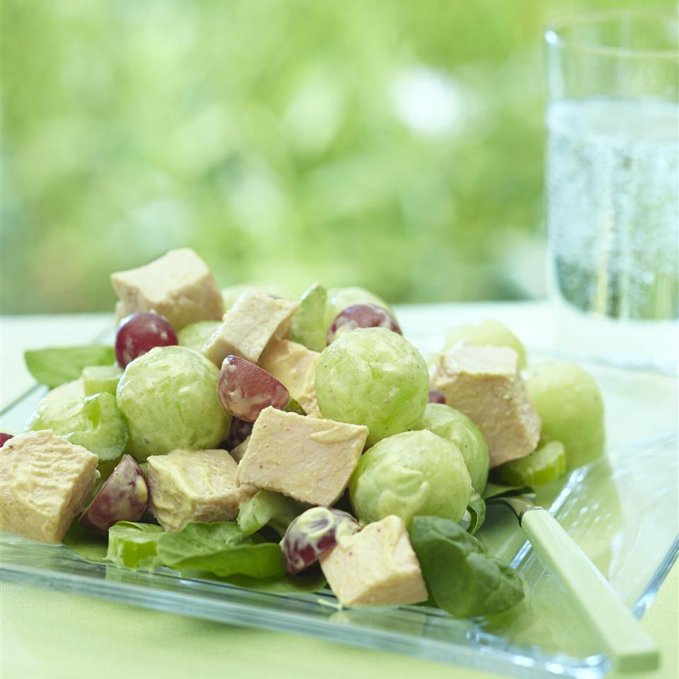 chicken salad with grapes and melon on glass plate