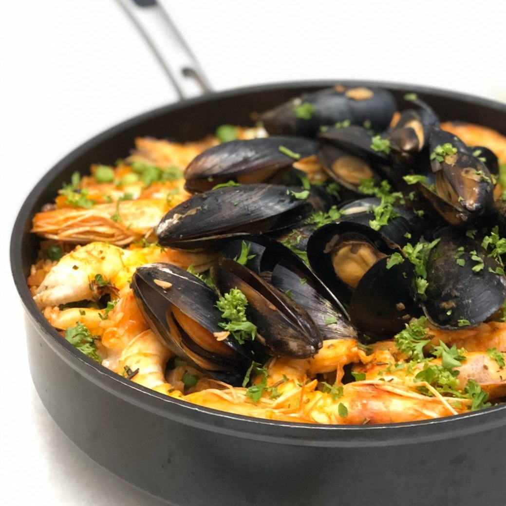 pan of homemade paella with shrimp, mussels, rice, and peas