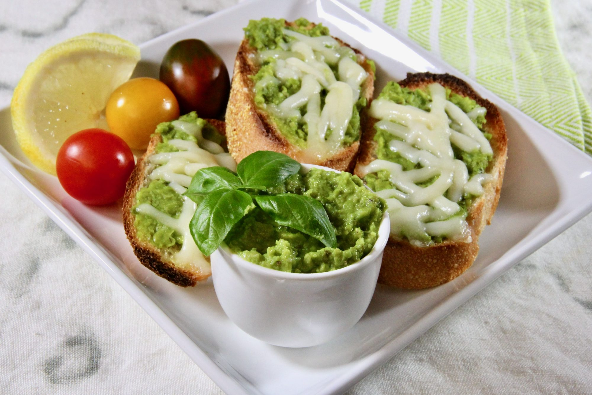 green pea pesto in a ramekin served with a tray of bread and tomatoes