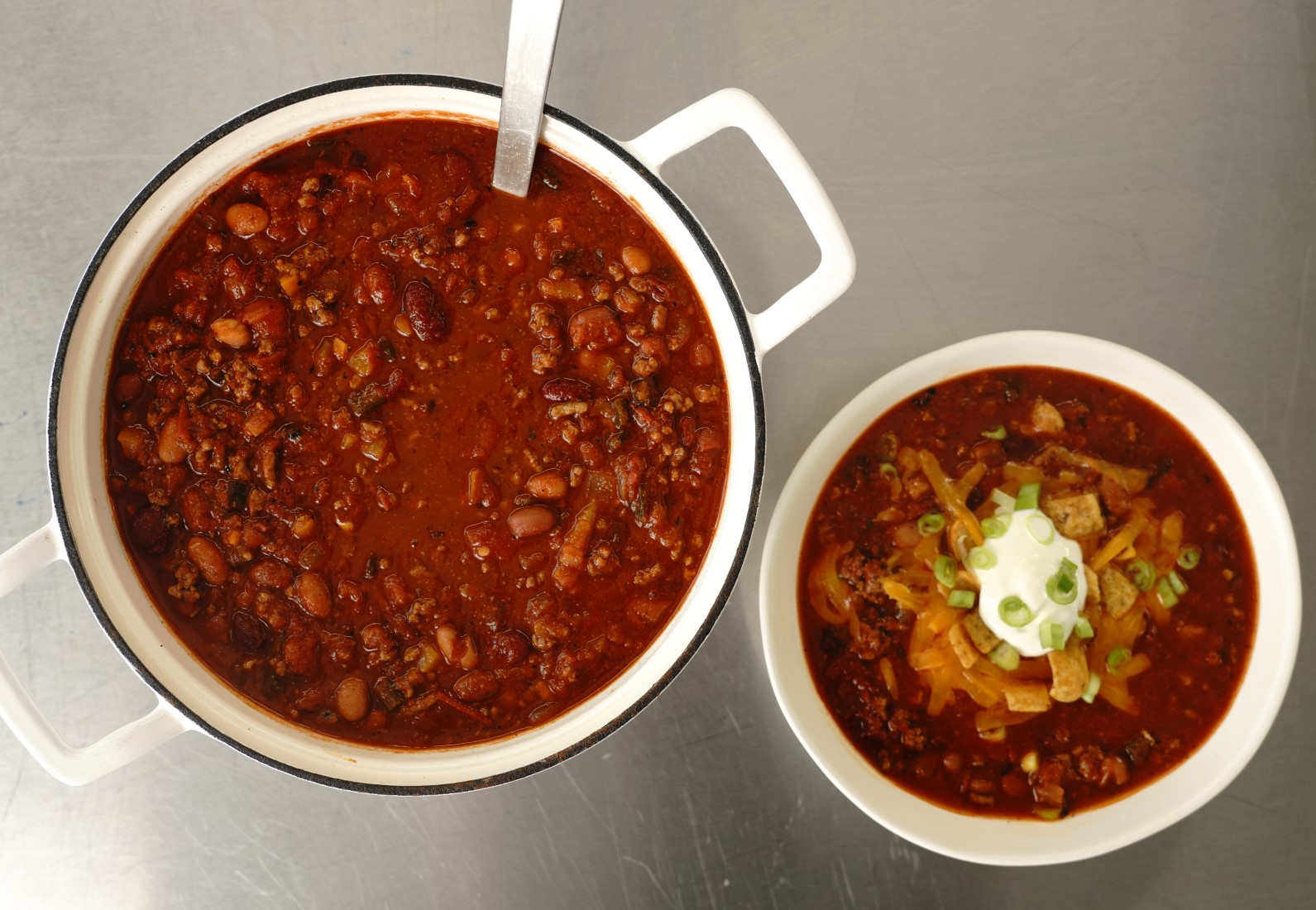 overhead shot of a pot of chili next to a bowl of chili topped with shredded cheese, corn chips, sliced scallions, and sour cream