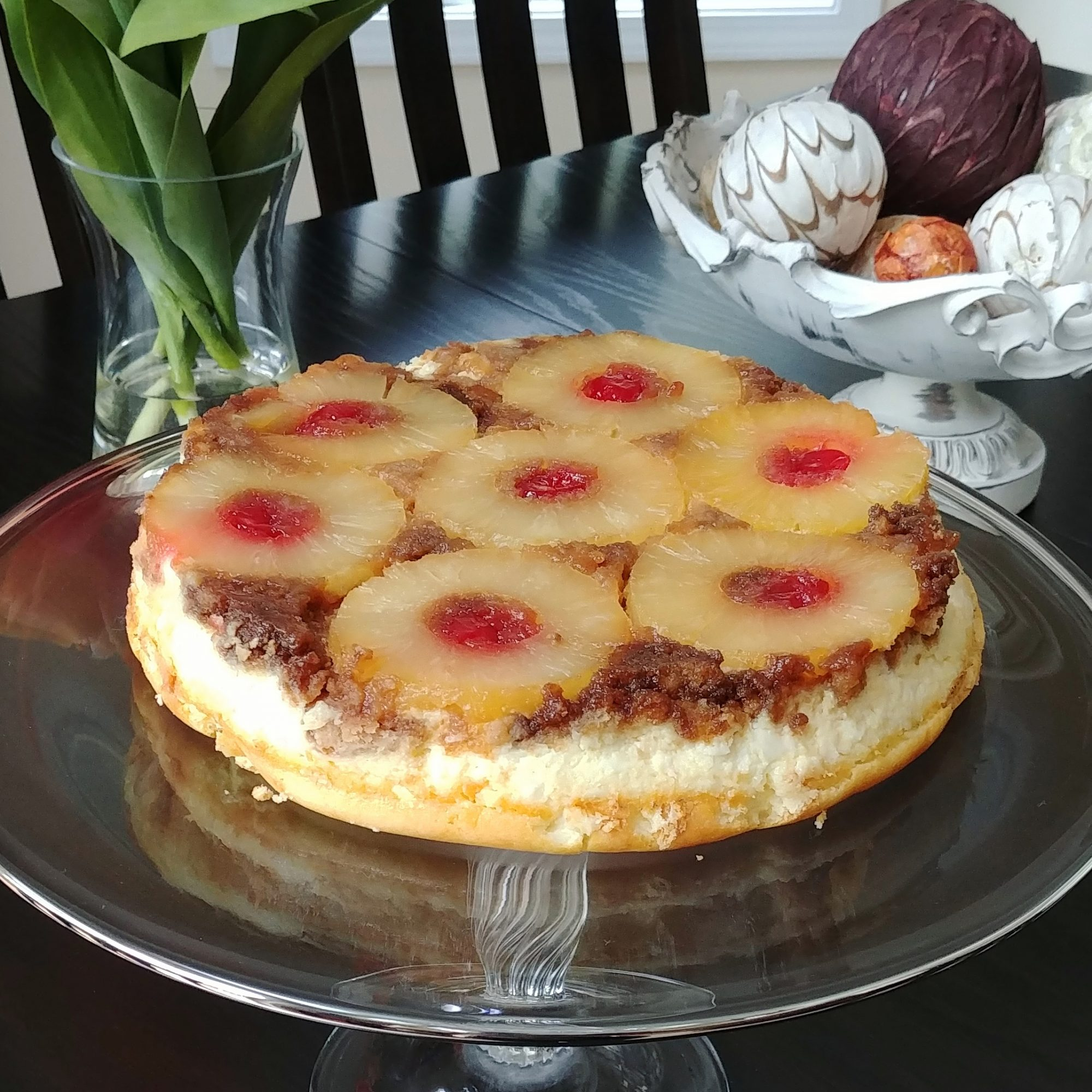 Pineapple Upside-Down Cheesecake on a glass cake stand