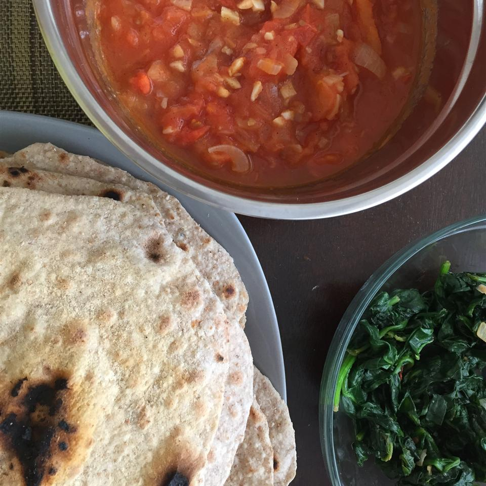 homemade whole wheat chapati flatbreads served with wilted greens, tomatoes, and onions