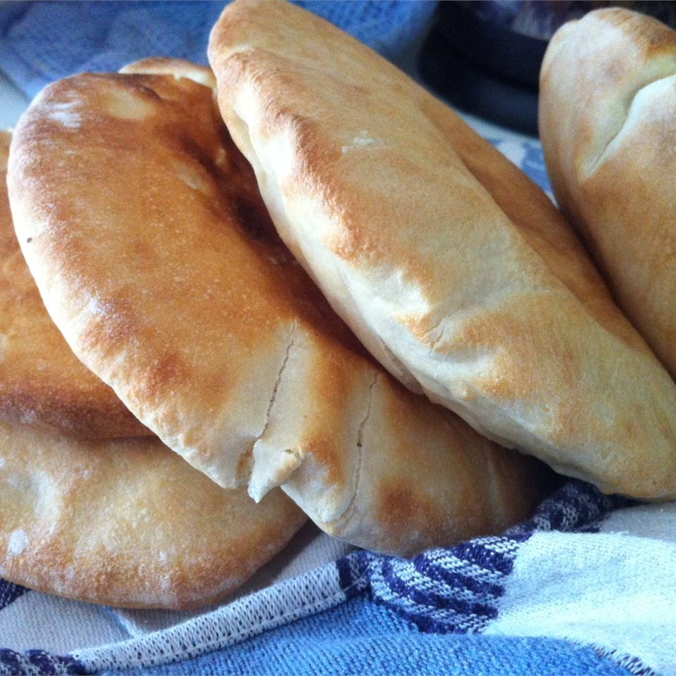 closeup of four homemade pita breads on kitchen towel