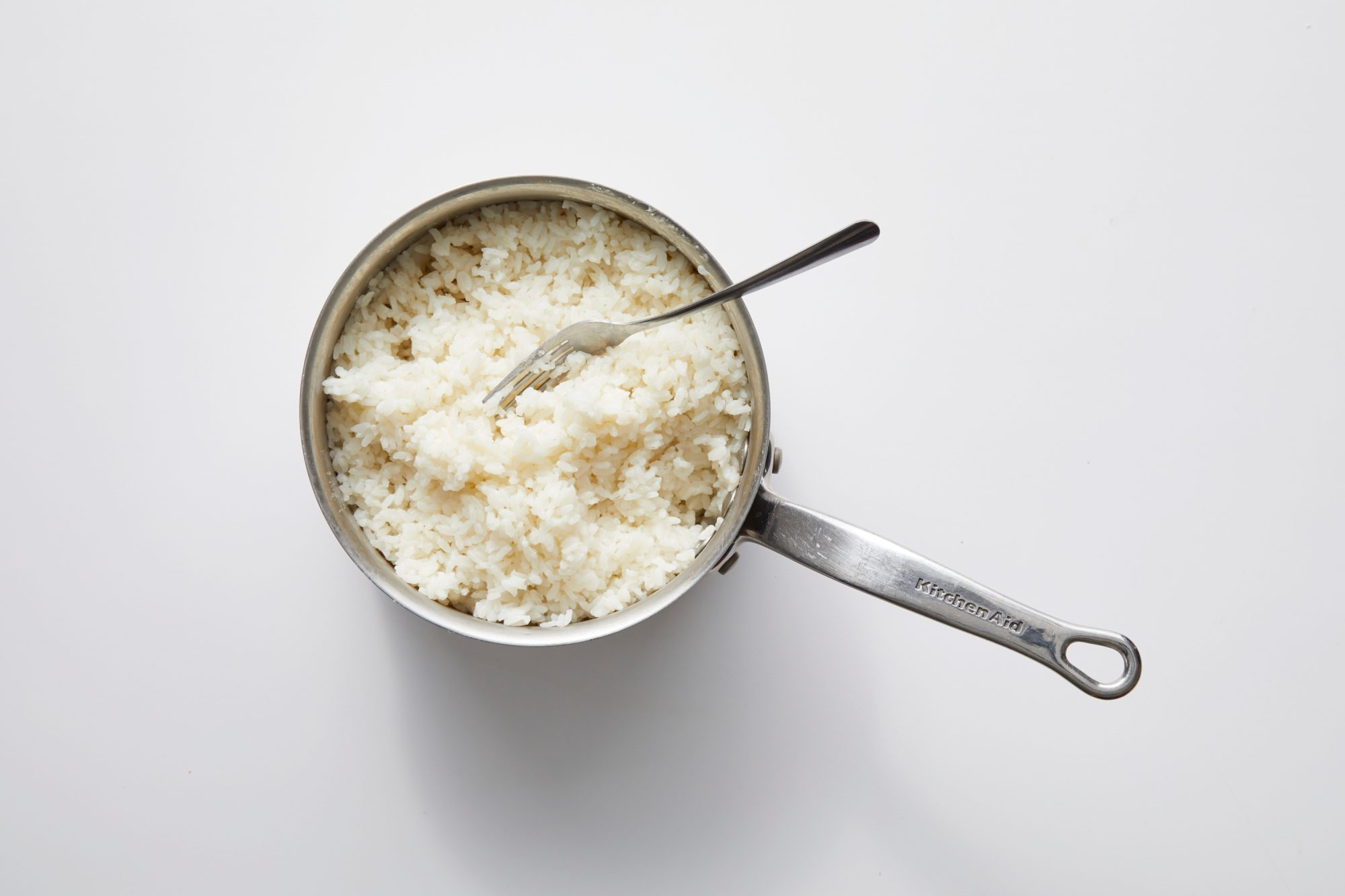 cooked white rice and fork in stainless steel KitchenAid saucepan on white background